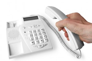 The hand holds telephone receiver above the phone